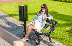 Woman in white dress sitting on bench at park with tablet Stock Image