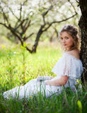Woman in white dress sitting on grass. Lovely woman in white dress sitting on grass near tree Stock Images