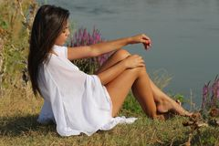 Woman in White Dress Sitting Beside River Royalty Free Stock Image