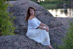 Woman in a white dress sitting Stock Photo