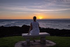Woman in a white dress sitting on a stone bench watching sunset royalty free stock images