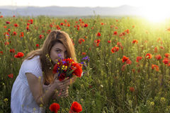 Woman in white dress smelling a bouquet of poppies Stock Photos