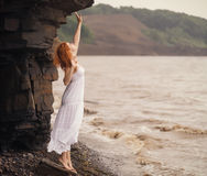 Woman in white dress standing on beach. Redhead woman in white dress standing on beach and looking to somewhere. Soft focus Stock Photo