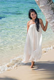Woman in a white dress standing on a sea beach Royalty Free Stock Photo