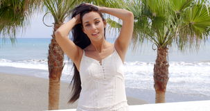 Woman in White Dress Standing on Tropical Beach. Waist Up of Attractive Brunette Woman Wearing White Summer Dress Looking Coy at Camera, and Standing Next to stock footage