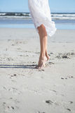 Woman in white dress stepping on the beach Royalty Free Stock Images