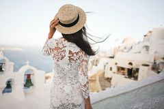 Woman in white dress and straw hat on Santorini island. Happy woman in white dress and straw hat enjoying her holidays on Santorini island. View on Aegean sea Royalty Free Stock Image