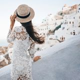 Woman in white dress and straw hat on Santorini island. Happy woman in white dress and straw hat enjoying her holidays on Santorini island. View on Aegean sea Stock Images