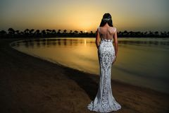 Woman in white dress in sunset beach stock images