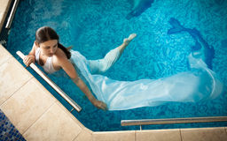 Woman in white dress swimming next to edge in swimming pool Royalty Free Stock Images