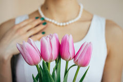 Woman in a white dress takes a gift of tulips Royalty Free Stock Images