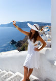 Woman in white dress is taking a selfie. At the village of Oia, Santorini Stock Images