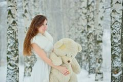 Woman in white dress with teddy bear Stock Image