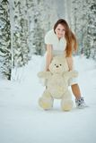 Woman in white dress with teddy bear Stock Photography