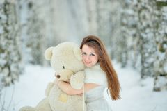 Woman in white dress with teddy bear Royalty Free Stock Photo