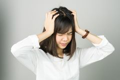 Woman in a white dress is touching head to show her headache. Causes may be caused by stress or migraine. stock images