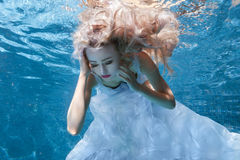 Woman in white dress under water pool. Stock Image