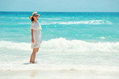 Woman in white dress walking on the beach Royalty Free Stock Photo
