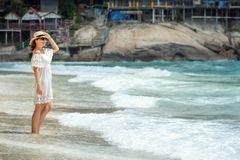 Woman in white dress walking on the beach Stock Image