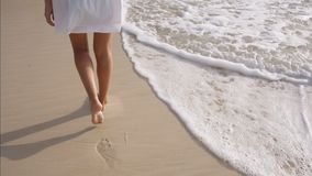 Woman legs leave footprints on the sand, wave washes away the footprints. A woman in a white dress walks on the sand, wave washes away the footprints stock video footage
