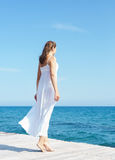 Woman in a white dress on a wooden pier Royalty Free Stock Images