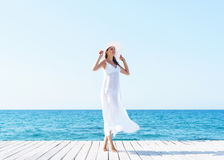 Woman in a white dress on a wooden pier. Woman in white dress on a wooden pier on summer.  Sea and sky background. Vacation, traveling and freedom concept Stock Photo