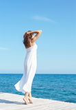 Woman in a white dress on a wooden pier Stock Photography