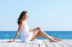 Woman in a white dress on a wooden pier. Woman in white dress on a wooden pier on summer.  Sea and sky background. Vacation, traveling and freedom concept Stock Image