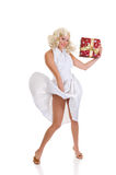 Woman white dress Xmas. Attractive young woman in classy white dress showing Xmas present.  Marilyn Monroe imitation. Studio shot, white background Royalty Free Stock Photos