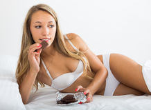 Woman in white eating chocolate Stock Photos
