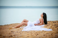 Woman in white fabric on beach Royalty Free Stock Images