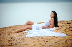 Woman in white fabric on beach Stock Photos