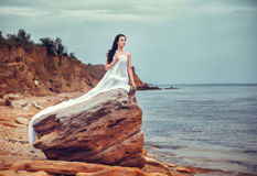 Woman in white fabric on the rock Royalty Free Stock Images