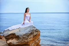 Woman in white fabric on the rock Stock Photos
