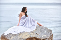 Woman in white fabric on the rock Stock Image