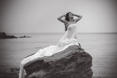 Woman in white fabric on the rock Stock Photo