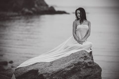 Woman in white fabric on the rock Royalty Free Stock Photos