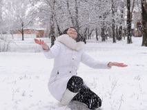 Woman in white and falling snow Stock Images