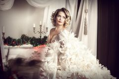Woman in white feather boa. Blonde in white feather boa. Horizontal frame on a light background Stock Photos