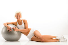 Woman in white fitness outfit exercise ball Royalty Free Stock Photos