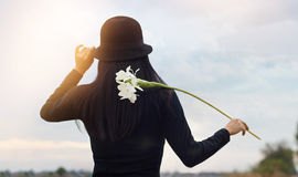 Woman with white flower in hand relaxing outdoor in rural landscape Royalty Free Stock Image