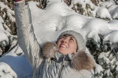 A woman with white frozen eyelashes and red cheeks in a gray hat and gray coat in a winter park stock image