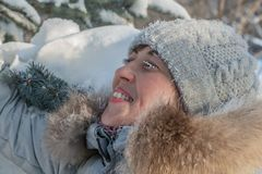 A woman with white frozen eyelashes and red cheeks in a gray hat and gray coat in a winter park royalty free stock photography