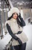 Woman with white fur cap and waistcoat enjoying the winter scenery near an iron fence. Attractive long hair brunette girl posing Royalty Free Stock Photos