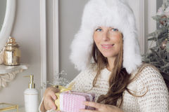 Woman in white fur hat, holding a birthday present. Portrait of a girl with a gift in hand Stock Photos