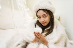 Woman with white fur hat and sweater drink coffee. Beautiful attractive woman with white fur hat and sweater drink hot coffee in house at winter. Smile girl Royalty Free Stock Images