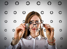 Woman in white with glasses. Woman in white is looking through the glasses. Oculist Ophthalmologist Doctor Point Examination Table Stock Photos