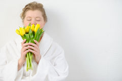 Woman in a white gown with a bouquet of fresh tulips. Royalty Free Stock Image