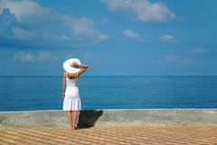 Woman in white hat looks at sea Royalty Free Stock Photography