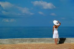 Woman in white hat looks at sea. Woman in white hat stand and looks at sea Stock Photo
